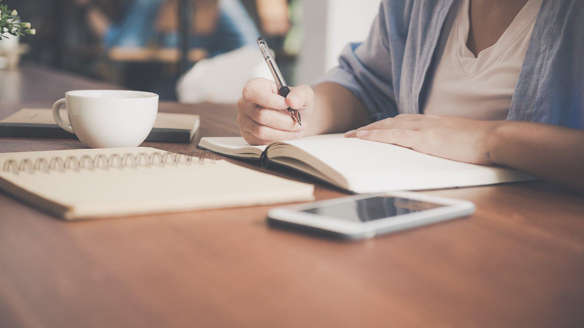 Henkilö kirjoittaa muistikirjaan pöydän ääressä.