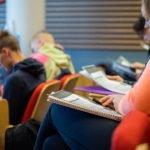 Opiskelijat lukevat luentomateriaalia luentosalissa.