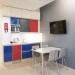 Keittiönurkkas jossa on tiskiallas, mikroaaltouuni, ruokapöytä ja televisio.