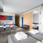Sporthotel-huone jossa on kaksi makuuhuonetta, keittiö ja sohva.