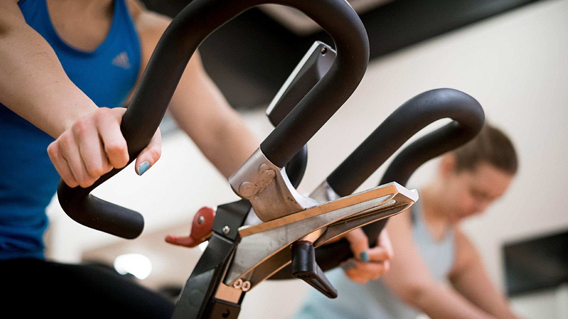 Kaksi naista polkee kuntopyörää spinning-tunnilla.