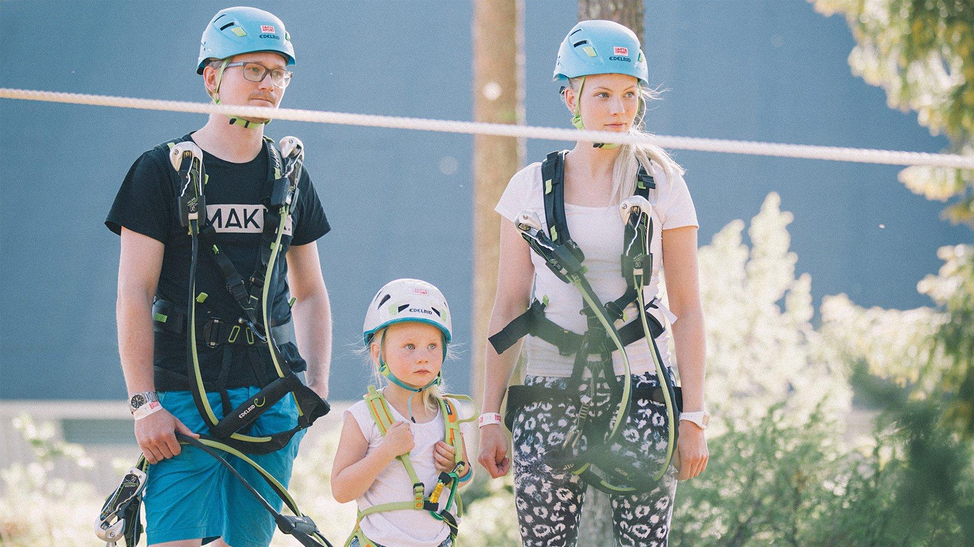 Isä, äiti ja pieni lapsi odottavat ohjeistusta kiipeilyvälineisiin pukeutuneena