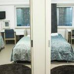 Kammi hostel huone jossa on kolme sänkyä ja kaksi työpöytää.