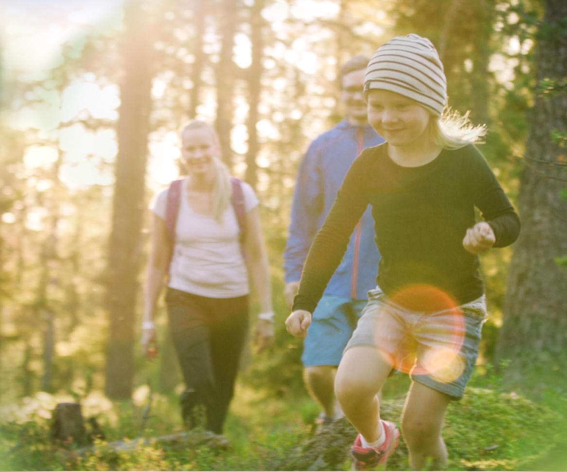 Lapsi juoksee kesäisellä metsäpolulla kahden aikuisen edellä.