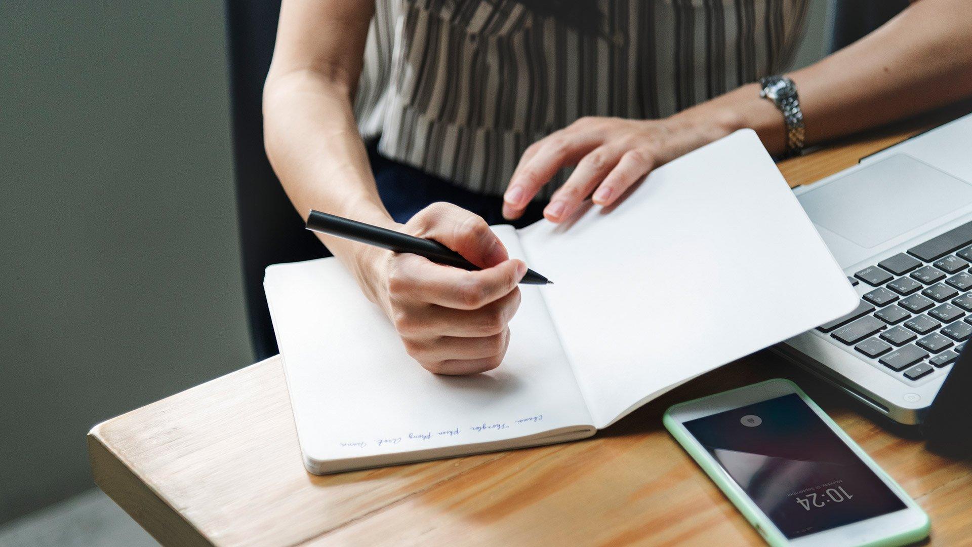 Henkilö kirjoittaa muistikirjaan.