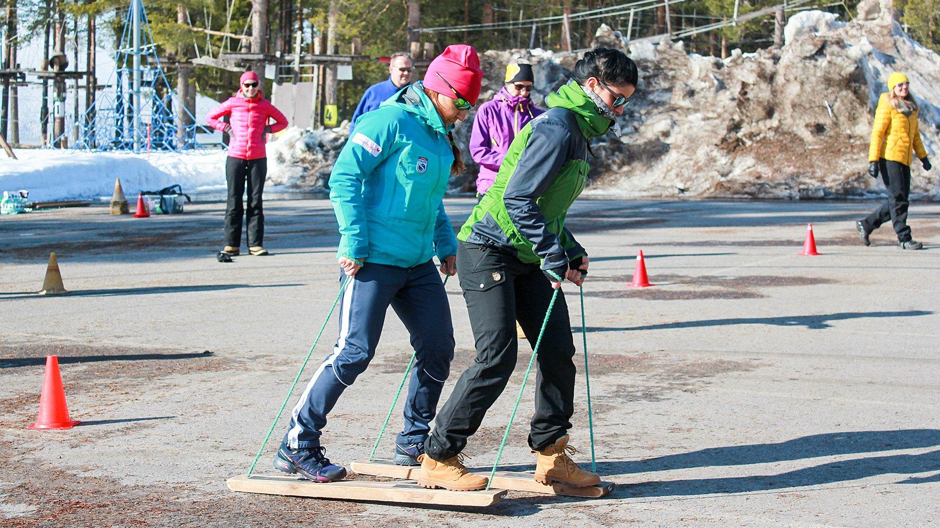 Kaksi henkilöä liikkuu tandem-suksilla parkkipaikan yli Santasport työhyvinvointi-olympialaisissa.